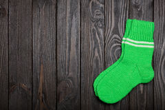 Knit green wool socks on dark wooden background. Royalty Free Stock Images