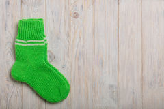 Knit green wool socks on light wooden background. Stock Images