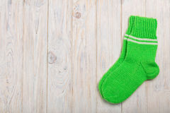 Knit green wool socks on wooden background light. Royalty Free Stock Images