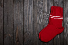 Knit red wool socks on dark wooden background. Royalty Free Stock Image