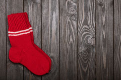 Knit red wool socks on dark wooden background. Royalty Free Stock Images