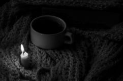 On a knit, warm scarf a candle lit, a cup of coffee stock photography