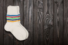 Knit white wool socks on dark wooden background. Royalty Free Stock Photography