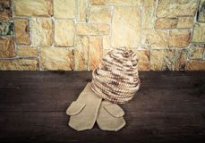 Knited hat and mittens on wooden table opposite a stony wall. To Stock Photo