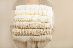 Stack of warm pastel sweaters, holding in womans hands. Knited sweaters stack in womans hands on beige wall Stock Photography