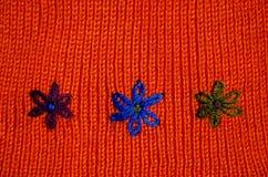 Knited ullbakgrund med blommasymboler Arkivbild