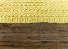 Knited yellow fabric.braid pattern on the wooden background. Royalty Free Stock Photos