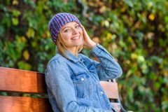 Knitted accessory for fall season. Autumn fashion accessory. Feel comfortable this fall with soft and warm stylish hat. Woman sit bench park nature background stock photography