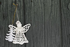 Knitted angel and xmas tree for christmas greetings card, and christmas. On old wooden background Royalty Free Stock Photo