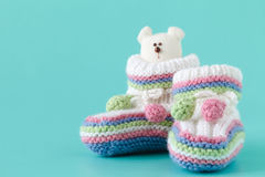 Knitted baby booties with toy Royalty Free Stock Photography