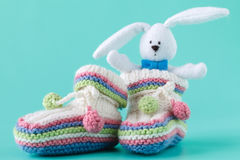 Knitted baby booties with toy Royalty Free Stock Photo