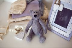 Knitted baby clothes and ultrasonic photo of your baby lie on the bed with a Teddy bear