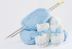 Knitted baby's bootees, yarn, needles Royalty Free Stock Photos