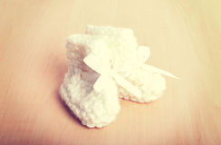 Knitted baby socks on against the backdrop Stock Images
