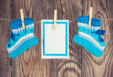 Knitted baby socks. And blank note hanging on clothesline against wooden background Royalty Free Stock Photos