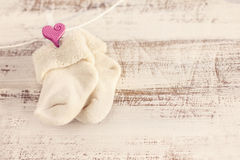 Knitted baby socks with pink heart on the wooden surface Royalty Free Stock Photos