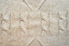 Knitted background. Pattern with braids and rhombus, wool neutral beige color Stock Photography