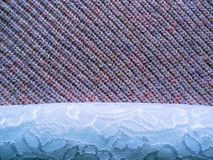Knitted background on which openwork white material royalty free stock photography