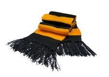 Knitted a barré le fil noir et jaune d'écharpe de laine sur le fond blanc Photo libre de droits