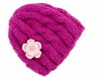 Knitted Beanie hat. Pink wool knitted winter hat with a small crochet flower motifs, Hand knitted, On a white background stock images