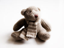Knitted bear. A knitted bear, sitting, with a scarf Royalty Free Stock Images