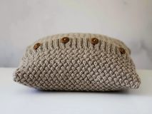 Knitted beige pillow with wooden buttons. Knitted beige chunky pillow with wooden buttons in white background Stock Image