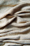Knitted beige wool fabric into the net with gold thread. Royalty Free Stock Images