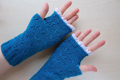 Knitted blue fingerless mitts Stock Images