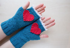 Knitted blue valentine's day fingerless mitts Stock Photos