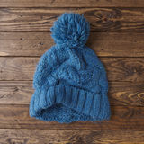 Knitted bobble hat. Knitted beanie on a wooden floor Royalty Free Stock Images