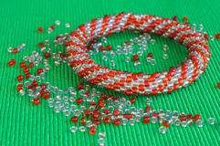 Knitted bracelet from red and gray beads Stock Photo