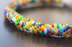 Knitted bracelet from small multi-colored beads Stock Image