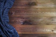 Knitted caldo ha strutturato la coperta grigio scuro su un fondo di legno Vista superiore, spazio per testo Fondo di caduta e di  immagine stock libera da diritti