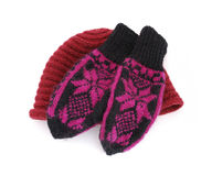 Knitted cap and mittens. Black woolen knitted mittens with purple ornament and red knitted cap isolated on a white background Stock Images