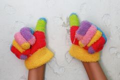 Knitted children's glove with colorful stripes and ok sign.  Royalty Free Stock Photography