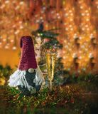 Knitted Christmas Santa Claus and a glass of champagne on the background of Christmas trees and garlands. Stock Photos
