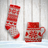 Knitted christmas stocking and red tea cup in front of white wooden wall, illustration Stock Photos