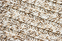 Knitted cloth. Knitted brown and white wool fabric, background Royalty Free Stock Images