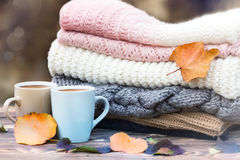 Knitted clothes coffee mugs on wood. Fall season mood icon. Royalty Free Stock Images