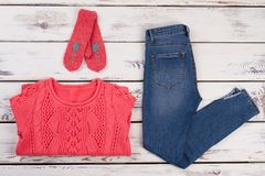 Knitted clothes and denim. Combination of red sweater, mittens and jeans. Stylish look from designer Royalty Free Stock Photography