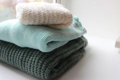 Knitted clothes of different colors on a white background. Knitted garments of different colors folded neatly on a white background Stock Photo