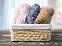 Knitted clothes rolled in bascket on wooden background indoors. royalty free stock image