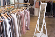 Knitted clothing on hangers in garment store Stock Photography