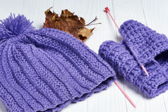 Knitted colorful scarf and hat on wooden background Royalty Free Stock Photography