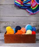 Knitted colorful striped mats and balls of bright woolen yarn in a wooden box on old wood wall background.  royalty free stock images