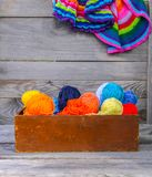 Knitted colorful striped mats and balls of bright woolen yarn in a wooden box on old wood wall background.  stock images