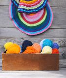 Knitted colorful striped mats and balls of bright woolen yarn in a wooden box on old wood wall background.  royalty free stock photo