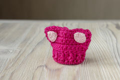 Knitted crochet small pink hat. Women`s hat for feminists march protest. Creative craft work. Knitted crochet small pink hat. Women`s hat for the feminists march stock image