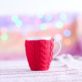 Knitted cup with christmas lights. Red knitted tea cup on glowing background Stock Photo