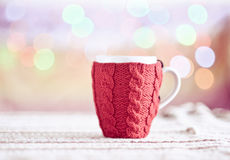 Knitted cup closeup. Red knitted cup on christmas background, closeup Royalty Free Stock Image